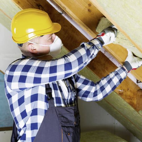 Worker with safety gear installing insulation.