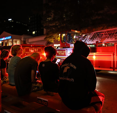 residents sitting in front of fire truck at night
